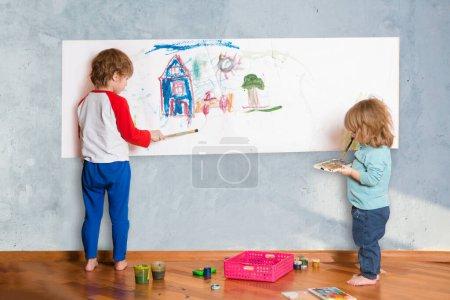 Photo pour Deux mignons petits enfants peignant sur le mur dans la chambre - image libre de droit