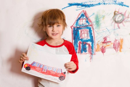 Photo for Cute little boy holds the drawing on paper - Royalty Free Image