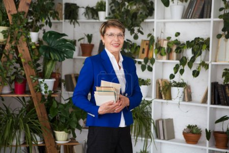 Photo for Happy senior woman with books indoors. - Royalty Free Image