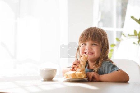 Photo pour Joyeux enfant girll manger croissant et boire du thé dans la cuisine blanche. - image libre de droit