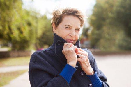 Photo pour Portrait femme âgée heureuse par une journée venteuse dans un environnement urbain d'automne - image libre de droit