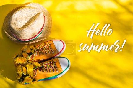 Photo pour Baskets jaunes et chapeau de paille sur fond avec ombres d'arbres avec espace de copie. Fin de la quarantaine. ombres profondes et longues. Bonjour l'été . - image libre de droit