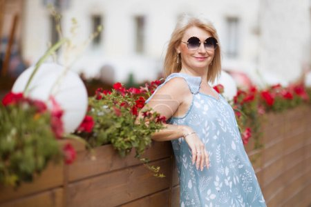Photo for Happy Elegant middle aged woman in sunglasses walks down the street in summer day. positive. positive. happy lifestyle concept - Royalty Free Image