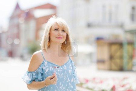 Photo pour Élégante femme d'âge moyen marche dans la rue le jour d'été. concept de voyage - image libre de droit