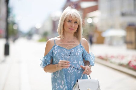 Photo for Elegant middle aged woman walks down the street in summer day. travel concept - Royalty Free Image