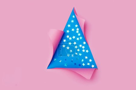 Photo for Confetti in the form of stars in triangular Torn hole and ripped of paper in a shape of Christmas tree. Christmas flat lay - Royalty Free Image