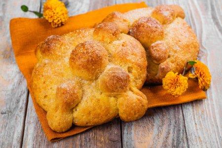 Photo pour Pan de muerto - pâtisserie traditionnelle, pain, petits pains avec orange et le sucre au four pour Mexicad journée des morts. Fleurs de souci - symbole de la mort sur fond en bois. Espace copie - image libre de droit