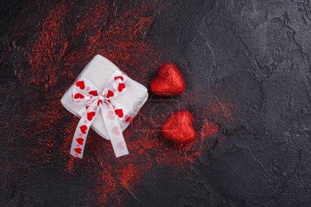 Photo pour Coeurs rouges scintillants et boîte cadeau sur fond sombre. Carte de voeux pour la Saint Valentin. Espace de copie - image libre de droit