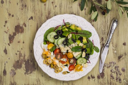 Photo for Delicious homemade cobb salad with avocado, egg, beet leaves, olives and tomatoes - Royalty Free Image