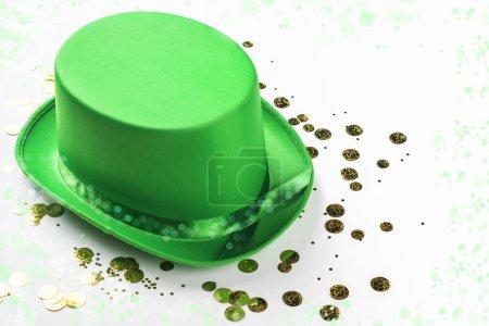 Photo pour St. Patricks Day fond avec chapeau de carnaval vert et confettis de pièces d'or sur table en bois blanc. Espace de copie - image libre de droit
