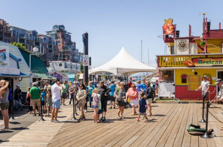 Victoria, BC, Canada - June 28, 2017: People Wandering around Fisherman's Wharf on a Summer Day. Fisherman's Wharf offers food kiosks, unique shops and eco-tour adventures in a working harbour setting.