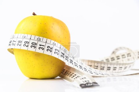 Photo for Yellow Apple and a Measuring Tape. Concept of Dieting. - Royalty Free Image