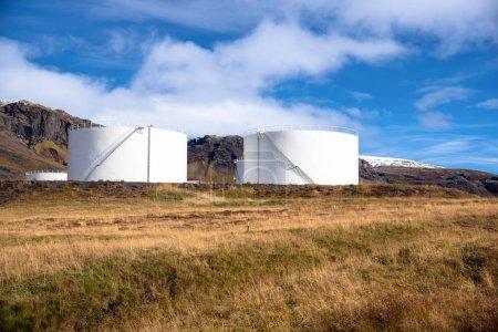 Photo pour Réservoirs de carburant blancs énormes au pied d'une montagne en Islande un jour d'automne clair - image libre de droit