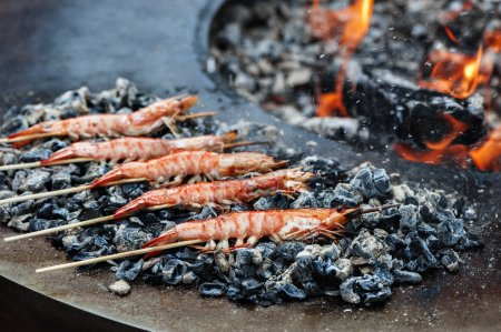 Photo for Shrimps grilled on wooden skewers laying near grill - Royalty Free Image
