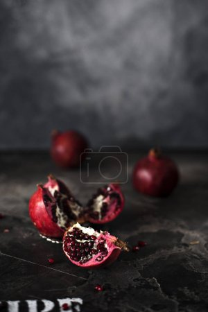 Photo for Red pomegranates on dark concrete background with copy space - Royalty Free Image