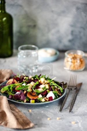 Photo for Delicious healthy salad with arugula and roasted mushrooms on plate, fork with knife, glass of water and ingredients on table - Royalty Free Image