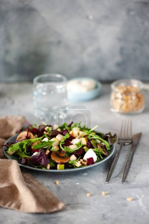 Photo for Close-up view of delicious healthy salad with arugula and roasted mushrooms on plate, fork and knife on table - Royalty Free Image