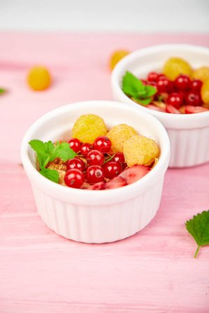 Photo for Healthy breakfast on white bowls. Fresh granola, muesli or cereal with berries - yellow raspberry, currents and strawberry on pink background. Diet food. Clear food. Copy space. - Royalty Free Image