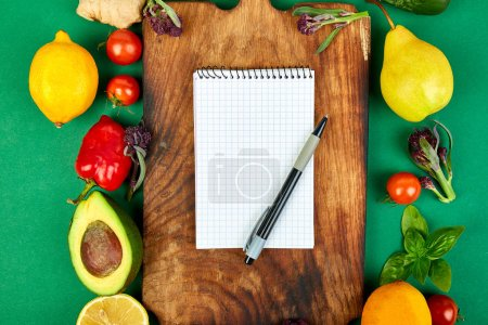 Photo for Shopping list, recipe book, diet plan. Fresh raw vegetables, fruit and  ingredients for healthy cooking. top view, place for text. Diet or vegan food, vegetarian and healthily cooking concept. Flat lay. Notepad for your recipe concept. - Royalty Free Image