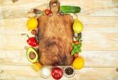 """Постер, картина, фотообои """"Свежие сырые овощи, фрукты и ингредиентов для здорового приготовления приготовление вокруг старинные разделочная доска на деревянных фоне, вид сверху, место для текста. Диета или вегетарианец, вегетарианские и здорового приготовления пищи концепции. Заложить квартиру."""""""