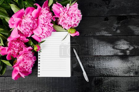Photo for Beautiful pink peony flowers on black background with note or diary. Planing to do list. Copy space Top view. Flat lay. Empty blank. - Royalty Free Image
