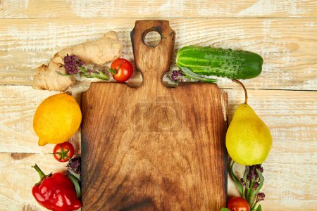 Photo for Fresh raw vegetables, fruit ingredients healthy cooking salad making around cutting board on wooden background, top view, place for text. Diet or vegan food, vegetarian and cooking concept. Flat lay. - Royalty Free Image