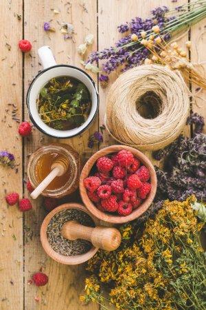 Photo pour Tasse à base de plantes décoction, Collection d'herbes médicinales Traitement des herbes sauvages Fond en bois Vintage Style rural, framboise, miel - image libre de droit