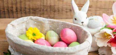 Photo for Easter, painted eggs in a basket on a wooden background, tulips, spring Christian holiday - Royalty Free Image
