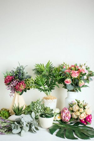 Photo for Various artificial flowers, bouquets in vases, succulents - Royalty Free Image