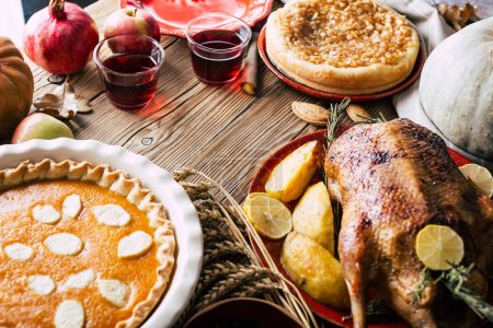 Photo for Thanksgiving dinner table with turkey, pumpkin and apple pie, top view - Royalty Free Image