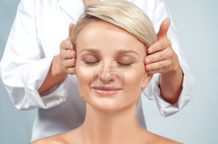 Photo for Beauty and facial treatment. Beautiful woman with clean perfect skin is getting face massage - Royalty Free Image