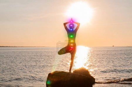 Photo pour Femme médite avec sept chakras lumineux sur la plage. Silhouette de la femme pratique le yoga au coucher du soleil sur le rivage de la mer. Méditation Kundalini . - image libre de droit