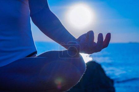 Photo pour Femme médite sur la plage calme au coucher du soleil. Femme pratique le yoga assis dans la pose Lotus au lever du soleil. Silhouette de femme méditant sur la plage - image libre de droit