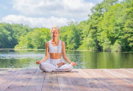 Photo pour Femme attrayante pratique le yoga et la méditation assis dans la pose de lotus près du lac. Jeune femme médite en plein air le matin . - image libre de droit