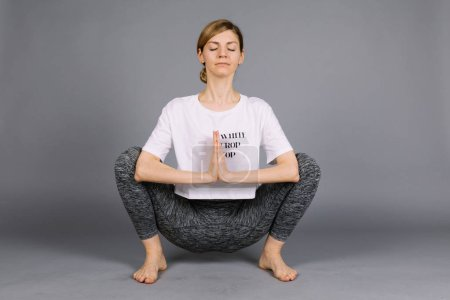 Sporty beautiful young woman practicing yoga, work...