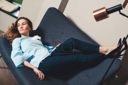 Photo pour Femme d'affaires élégant prenant une pause. Belle jeune femme allongée sur le canapé gris dans un bureau modern. Fille Fashion reposant sur le canapé en hauts talons de chaussures élégantes. Concept mode, beauté et style de vie. - image libre de droit