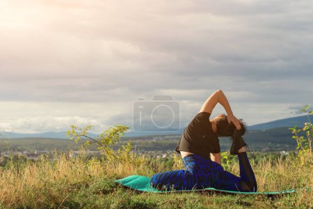Photo for Yoga exercise outdoors. Young woman sits in yoga pose on rock. Freedom, calmness and relax, woman happiness. Toned image. Lifestyle and healthy concept. Back view of woman practices yoga on nature - Royalty Free Image