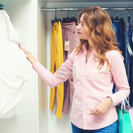 Photo for Smiling elegant woman choosing clothes in luxury store. Sale, consumerism, and people concept. Girl with wavy hair, in pink shirt and trendy jeans in shop. Happy shopping time. Seasonal sales - Royalty Free Image