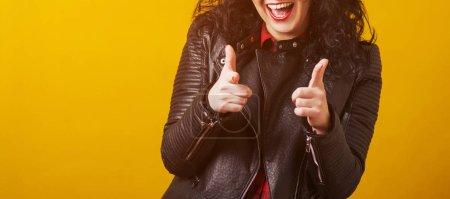 Photo pour Hipster girl sourire, en agitant les mains sur fond jaune. Jolie fille bouclée dans une veste en cuir moderne, pointant du doigt sur vous, vous voulez. Espace de copie. Succès, confiance, concept gestuel - image libre de droit