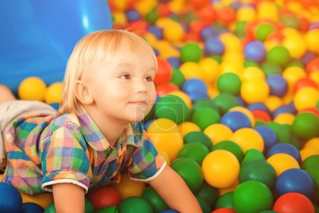 Photo for Happy baby at playground. Little child at indoor play center. Happy childhood. Child playing with colorful balls in playground ball pool. Child boy playing and smiling - Royalty Free Image