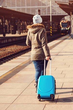 Photo pour Jeune touriste marchant, traînant sac valise de bagages. Une fille à la gare. Concept de voyage. Mode de vie, voyages, vacances. Automne, voyage d'hiver. Femme dans le chapeau avec la valise vue arrière - image libre de droit