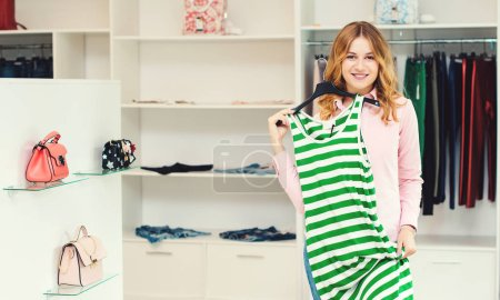 Photo for Happy woman shopping in clothing store. Sale, fashion, consumerism and people concept. Young woman choosing clothes in mall. Shopping time. Beautiful girl enjoying purchase at store. Seasonal sales - Royalty Free Image