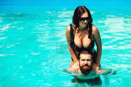 Photo for Romantic sensual couple relaxing in swimming pool. Bearded guy having fun with sexy hot girlfriend. Summer vacation. Happy lovers on honeymoon travel. Luxury resort hotel. Young handsome couple - Royalty Free Image