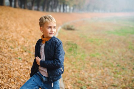 Photo for Lovely blonde boyon a walk in an autumn park. Stylish kid outdoors. Schoolboy wearing fashion clothes posing outdoors. Autumn fashion concept. - Royalty Free Image
