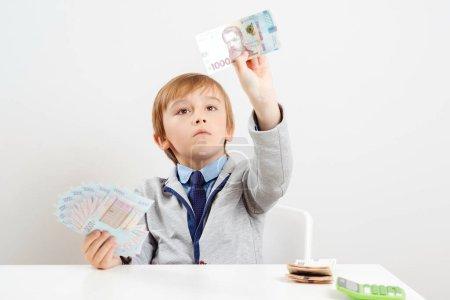 Cute little businessman calculates money. Money an...