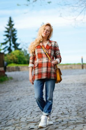 Photo for Young stylish hipster woman walking on the street. Girl wearing trendy outfit. Woman enjoy her weekends, travel. Lifestyle fashion portrait. Street fashion style. Cool girl with blonde long hair posing at street. - Royalty Free Image