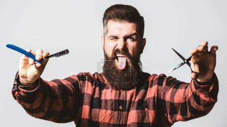 Photo for Brutal barber with straight razor and scissors. Bearded guy showing tongue. Barber shop, service. Mens haircut. Vintage barbershop, shaving. Barber scissors. Vintage straight razor. Barbershop. - Royalty Free Image