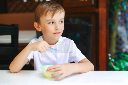 Photo for Cute little boy eating ice cream at outdoor cafe. Happy kid eating favorite icecream. Happy childhood. Summer holidays. Childrens day. Summertime. - Royalty Free Image