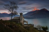 Little church Santa Eufemia in Musso over Lago di Como with mountains in sunset light in background, Italy