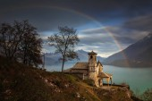 Rainbow over little church Santa Eufemia in Musso over Lago di Como with mountains in background, Italy